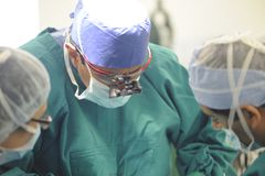 Concentrerende chirurgen die handeling uitvoeren stock foto's