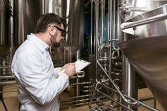 Concentrerende mens die nota's maken bij bierfabriek Stock Fotografie