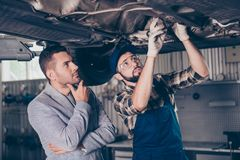 Concentreted focused expert in checkered shirt and cap and pensive ponder businessman in grey smart formal suit, under the car, l. Ooking up. Engine, motor royalty free stock images