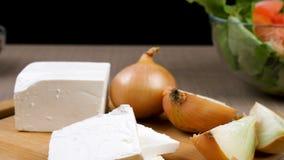 Concentrez dépister le chariot sur la salade de tomates avec les lefs de salade verte, l'oignon et le feta sur le conseil en bois banque de vidéos