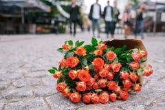 Concentrez sur le groupe de roses en papier de métier sur la rue de gris de pavage Photo libre de droits