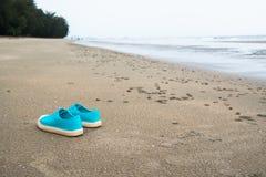 Concentrez sur une paire d'espadrilles bleues sur la plage Image libre de droits