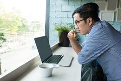 Concentri l'uomo d'affari asiatico con gli occhiali che funzionano con astuto fotografie stock