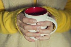 Concepção do delicado e do borrão Uma mulher guarda um copo quente do chá e aquece suas mãos Imagens de Stock Royalty Free