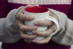 Concepção do delicado e do borrão Uma mulher guarda um copo quente do chá e aquece suas mãos Imagens de Stock