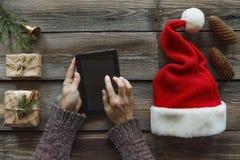 Concepção: Preparação de presentes do Natal Um homem guarda um PC da tabuleta em suas mãos e embala presentes de Natal Foto de Stock Royalty Free