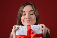 Concepr of receiving long awaited presents on Christmas. Close up photo portrait of attractive pretty lady with pink lips lipstick. Holding big present in hans Royalty Free Stock Photography