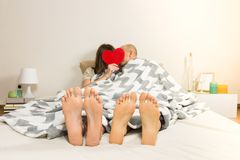 Young couple kisses in bed in minimalistic modern bedroom. Conceprt of engaged female and male persons hiding faces behind red heart shape, focus on their feet stock photography