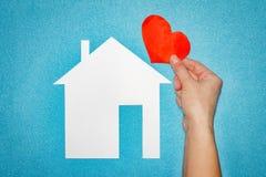 Concept à la maison d'amour main femelle avec le coeur rouge au-dessus de la maison de livre blanc sur le fond bleu Image stock