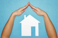 Concept à la maison d'assurance Mains sous la forme de toit au-dessus de maison du livre blanc sur le fond bleu images stock