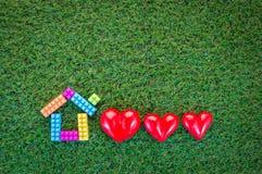 Concept à la maison doux à la maison avec le modèle à la maison et trois coeurs rouges dessus Photo stock