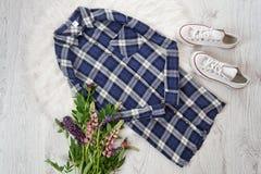 concept à la mode Chemise à carreaux, espadrilles et bouquets des fleurs Photo stock