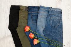 concept à la mode Cinq paires de jeans de différentes couleurs, roses oranges photographie stock libre de droits