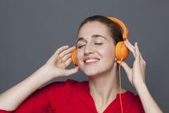 Concept à la mode d'écouteurs pour la fille 20s joyeuse Photographie stock