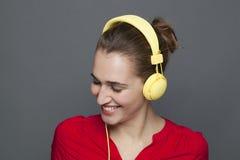 Concept à la mode d'écouteurs pour le beau sourire de la fille 20s Image libre de droits