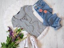 concept à la mode Style de rue Chemise grise avec le laçage, les jeans, les espadrilles et les bouquets des fleurs Photos libres de droits