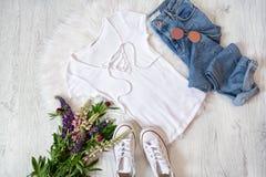 concept à la mode Style de rue T-shirt blanc avec le laçage, les jeans, les espadrilles et les bouquets des fleurs Image libre de droits