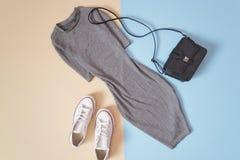 concept à la mode Style urbain du ` s de femmes Robe grise, espadrilles blanches et sac à main noir sur un fond bleu mou Photo stock