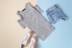 concept à la mode Style urbain du ` s de femmes T-shirt gris, espadrilles blanches et shorts de jeans sur un fond bleu mou Image stock