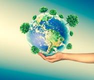 Concept écologique de l'environnement avec la culture des arbres au sol dans les mains La terre de planète physique Photos stock