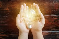 Concept économiseur d'énergie Une ampoule placée sur la main du ` s de femme photographie stock