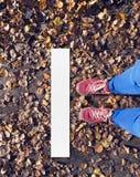 Concept aanvang nieuw met vrouwenbenen in rode schoenen en jeans royalty-vrije stock foto