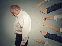 Concept of accusation guilty businessman person. Side profile upset old man looking down many fingers pointing at him isolated grey office wall background Royalty Free Stock Image