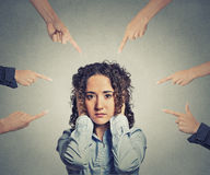Concept accusation guilty woman many fingers pointing at her. Concept of accusation of guilty businesswoman many fingers pointing at her. Portrait sad unhappy Stock Image