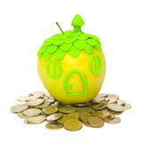 Concept of acquisition and real estate insurance. The Image of an apple on a heap of coins Royalty Free Stock Image