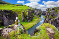 The concept of active northern tourism. The striking canyon Fyadrarglyufur in Iceland. The elderly woman standing on a rock and photographing the scenic Stock Photography