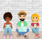 The concept of active users of gadgets. Young people sitting on the floor using gadgets. Happy people Royalty Free Stock Photo