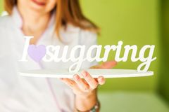 The concept of aesthetic . A woman holds an inscription in her hands. I love sugaring. royalty free stock images
