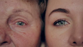 Concept of aging and skin care. face of young woman and an old woman with wrinkles. Concept of aging and skin care. face of young woman and an old woman with stock footage