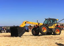 The concept of agronomy, a yellow tractor with a bucket demonstrates work at the annual exhibition, Ukraine, Nikolaev September 1. 5, 2017. The concept of stock image