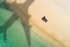 Concept of airplane travel to exotic destination with shadow of commercial airplane flying above beautiful tropical beach. Beach stock images