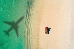 Concept of airplane travel to exotic destination with shadow of commercial airplane flying above beautiful tropical beach. Beach royalty free stock photos