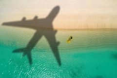 Concept of airplane travel to exotic destination with shadow of commercial airplane flying above beautiful tropical beach. Beach stock image