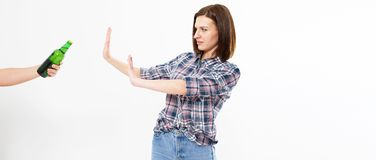 A concept of alcoholism. A young woman saying no sign to alcoholic beverage bottles stock image