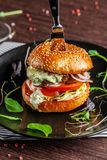 Concept américain de cuisine Un hamburger juteux de viande avec un grands klateyta, tomate, concombre, ketchup et salade Faisant  photo libre de droits