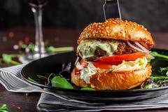 Concept américain de cuisine Un hamburger juteux de viande avec un grands klateyta, tomate, concombre, ketchup et salade Faisant  photographie stock libre de droits