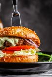 Concept américain de cuisine Un hamburger juteux de viande avec un grands klateyta, tomate, concombre, ketchup et salade Faisant  photographie stock