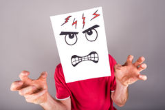 Concept of anger. Man behind a paper with a anger expression stock photos