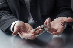 Concept of appraising precious goods for work. Male appraiser's hands with diamond bracelet royalty free stock photography