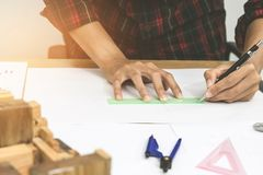 Concept architects,engineer holding pen pointing equipment architects On the desk with a blueprint. In the office, Vintage, Sunset light.Selective Focus stock images