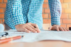 Concept architects,engineer holding pen pointing equipment architects On the desk with a blueprint in the office, Vintage. Sunset light.Selective Focus royalty free stock image