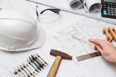 Concept architects or engineer holding pencil pointing equipment architects. On the desk with a blueprint in the office. Concept architects or engineer holding royalty free stock photo