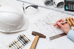 Concept architects or engineer holding pencil pointing equipment architects. On the desk with a blueprint in the office. Concept architects or engineer holding royalty free stock photos