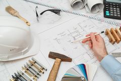 Concept architects or engineer holding pencil pointing equipment architects. On the desk with a blueprint in the office. stock photography