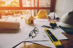 Concept architects, equipment architects On the desk with a blueprint in the office, Vintage, Sunset light. Selective Focus stock photography