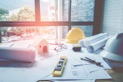 Concept architects, equipment architects On the desk with a blueprint in the office, Vintage, Sunset light. Selective Focus royalty free stock photography